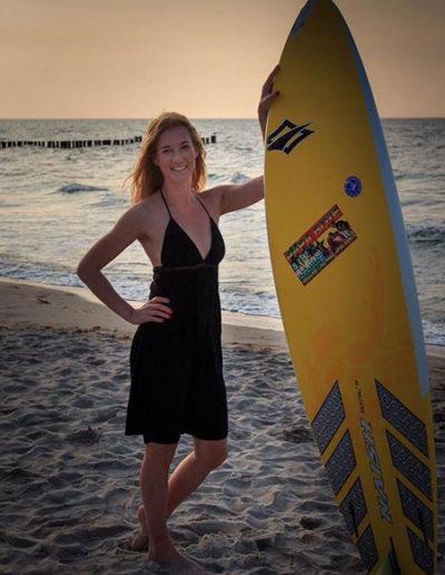 Model mit schwarzem Kleid und Surfboard am Kühlungsborner Strand